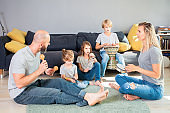 happy  family playing musical instruments at home,relaxed while sitting at the floor