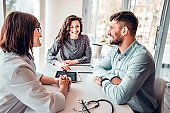 Side view image of happy young family at doctor appointment, enjoying good results of progressive therapy after medical tests. Health and medicine concept