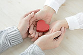 Heart object covered by man and woman's hands