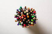 A lot of multi-colored pencils in a glass on a white background. View from above. School or art workshop.