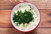 Step by step cooking of egg salad with leek and dill, step 3 adding chopped fresh dill, selective focus, top view