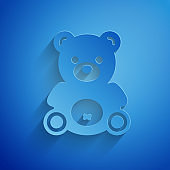 Paper cut Teddy bear plush toy icon isolated on blue background. Paper art style. Vector Illustration