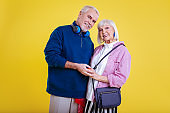 Retired couple wearing modern stylish clothes smiling broadly