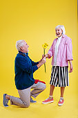 Retired man standing on knee presenting sunflower to wife