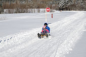 Mother and daughter sliding down on an Austrian toboggan during winter day