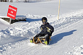Young boy sliding down on an Austrian toboggan during winter day