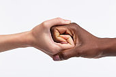 Women with white skin shaking hand of her dark-skinned friend