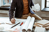 Interior designer holding pencil while painting plan for the room