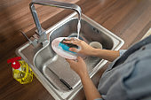 Housewife holding a plate under running water