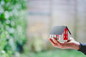 New home and house concept: Red house model outdoors in male hand, copy space