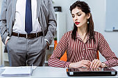 Flawless long-haired woman in striped blouse sitting on working place concept against sexual harassment