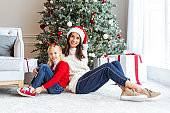 Mother and child sitting near the Christmas tree