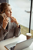 Attractive young woman talking on cellphone in cafe