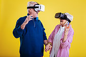 Husband holding hand of his wife while wearing VR glasses