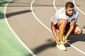 Calm fit African American male runner tying laces