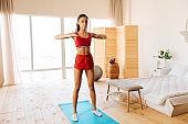 Slim and fit woman exercising on blue sport mat in the bedroom