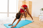 Slim woman with nice braids enjoying yoga workout in the bedroom