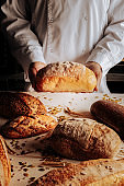 Professional baker showing different kinds of just baked bread