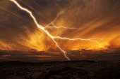 Lightning striking towards the ground. Lightning during a thunderstorm on a sunset