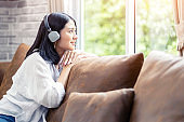 Asian woman sitting on sofa with headphones listen to music from smart phone and looking out of the window, resting and relaxation time at living room.