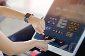 Woman hand with smart watch on wrist, wearable fitness device, Sporty runner doing exercise running indoor, taking weight loss with machine aerobic. Healthy sport cardio strong.