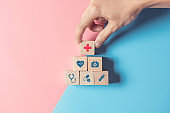 Health Insurance Concept, Hand of man arranging wood cube stacking with icon healthcare medical on pastel blue and pink background.