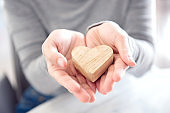 Female hands giving wood heart, Love concept for valentines day.