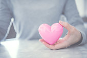 Female hands holding pink heart, Love concept for valentines day with sweet and romantic moment, copy space