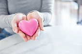 Female hands giving pink heart, Love concept for valentines day, copy space