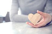 Female hand holding a wood heart shape, copy space.