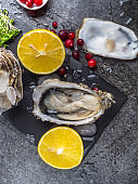fresh oysters in stone slate with ice, cranberries, lemon slices, delicatessen expensive food, rich in zinc, antioxidants, vitamin