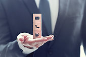 CONTACT US, Businessman holding three wooden blocks in his hand with icon telephone, mail and email.