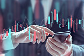 Businessman using a mobile phone to check stock market data, Technical price graph and indicator, Double exposure.