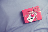 Gift box with love tag and heart on gray background.