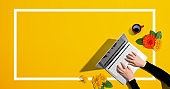 Person using a laptop computer with autumn flowers