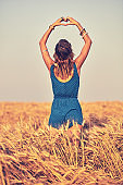 Girl holding heart-shape symbol for love in a wheat field.