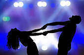 Silhouettes of a young couple dancing at live concert.