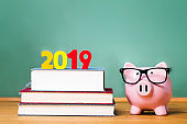 Class of 2019 theme with textbooks and piggy bank