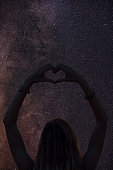 Silhouette of a girl holding heart-shape symbol for love on a starry night sky. My astronomy work.