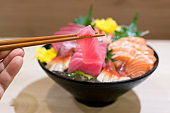 Chopsticks with Tuna sashimi with Mixed sliced fish sashimi on ice in black bowl. Sashimi Salmon Tuna Hamachi Prawn and Surf Calm set, raw fish, japanese food in Asian restuarant.