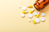 Multicolor tablets and pills capsules from glass bottle on yellow background Close-up