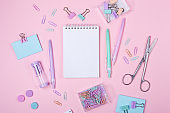 School background with notebook and pastel colorful study accessories on pink background Back to school concept