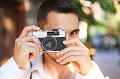 Half length of young beautiful man outdoor in the city holding instant camera, shooting - photography, creative, artist concept.