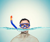 Happy funny man in a swimming mask awith snorkel is in the water. Sea holiday concept.