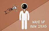 "cup of coffee and a drawn person in a Wake Up concept on paper background  with the message ""wake up, new ideas"""
