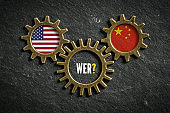 three cogwheels on slate background with the flags of USA and the China and the word 'Who?' in German in the middle