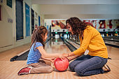 Mother and daughter with bowling ball