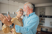 Smiling mature couple dancing at home