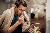 Ill man looking at digital tablet