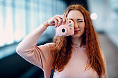 Positive redhead young female with instant camera